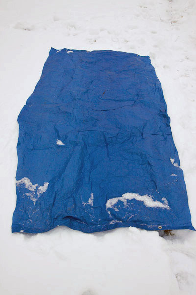 a long blue plastic tarp cut to tent shape